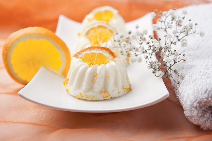 Badepralinen mit Orangenduft auf einem Teller mit Orangenscheiben in Kuchenform