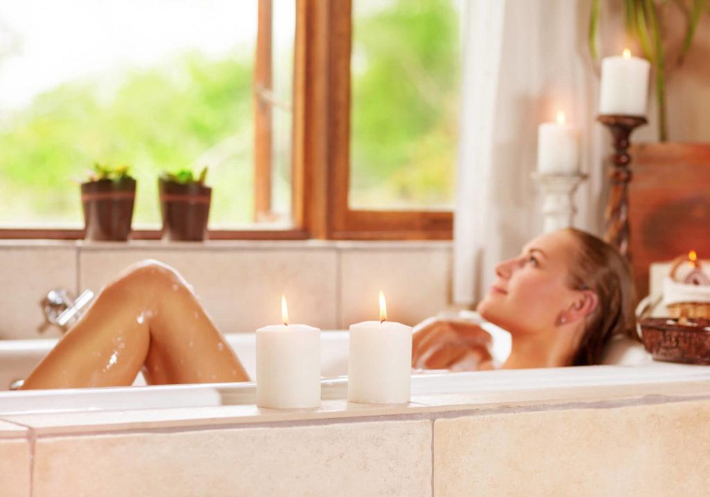 Eine Frau genießt ein Bad mit Badekugeln und schaut aus dem Fenster